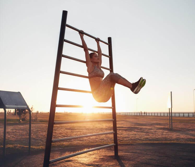 woman exercising on wall bars