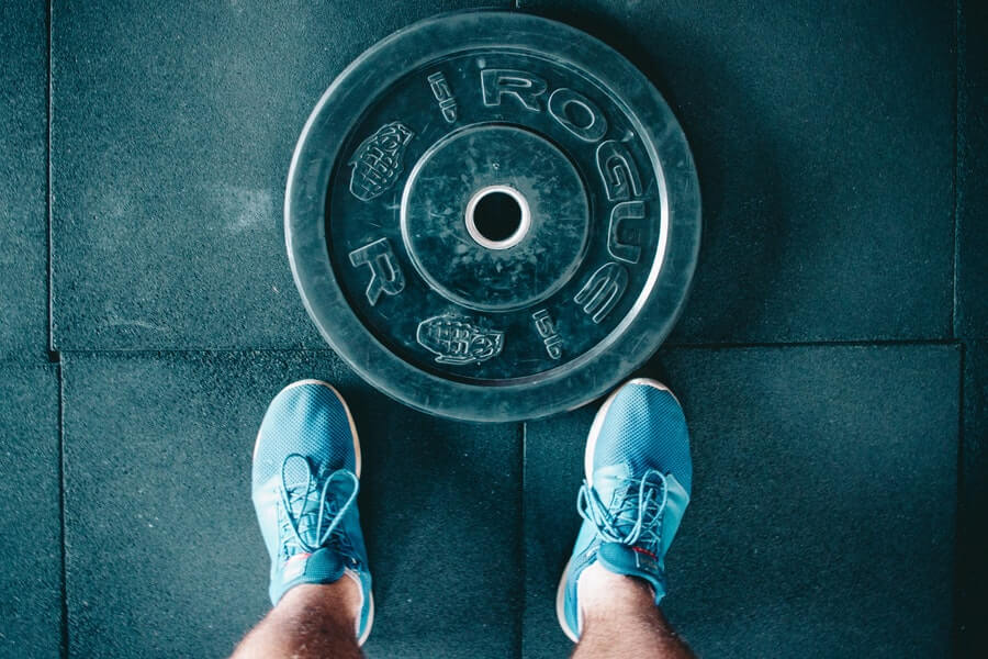 Rogue bumper plate and pair of workout shoes