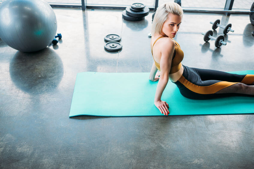 athletic woman resting on fitness mat after workout