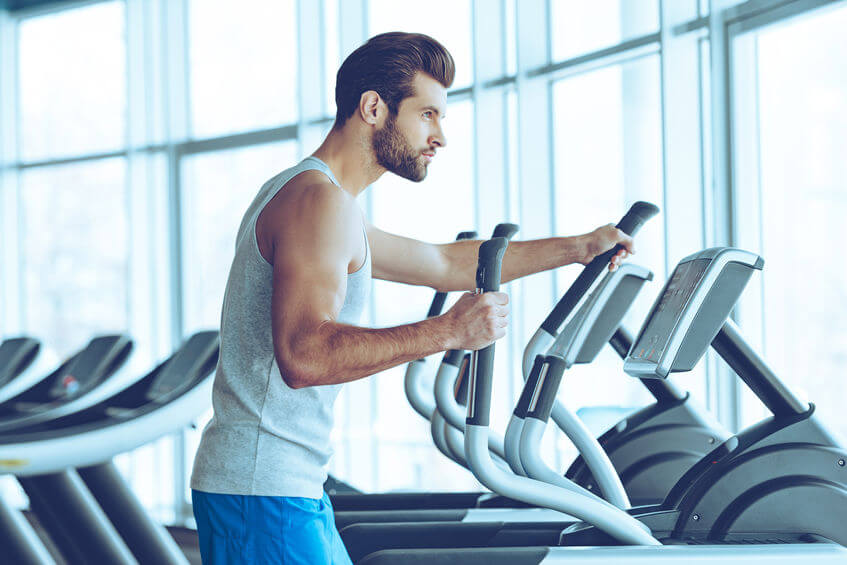 man working out on elliptical machine