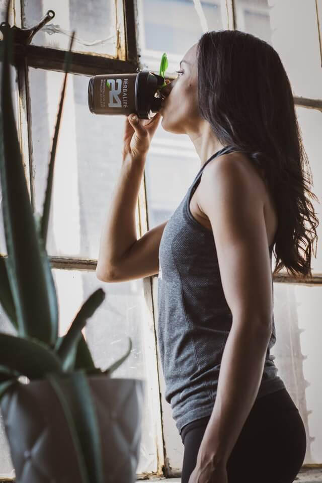 woman drinking pre-workout drink