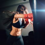 woman punching heavy bag with boxing gloves