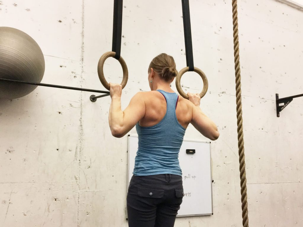 woman using gymnastic ring in crossfit gym
