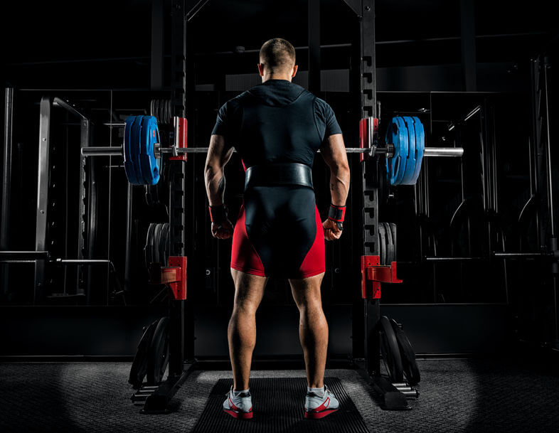 athlete stands in front of the power rack with a barbell