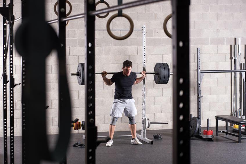 man lifting barbell on squat rack