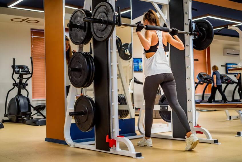 woman doing squats on smith machine