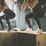 two girls jumping on plyo box in fitness class
