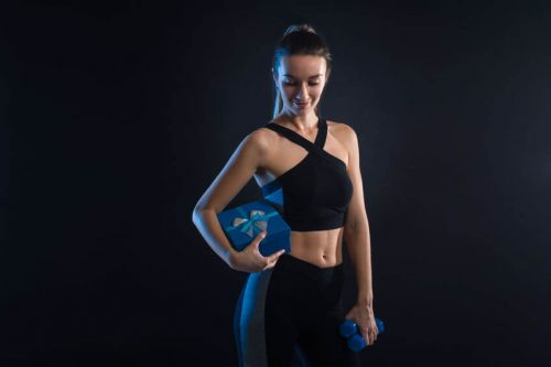 fitness woman holding dumbbells and gift box in her hands