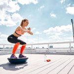 athlete girl work out with Bosu ball trainer