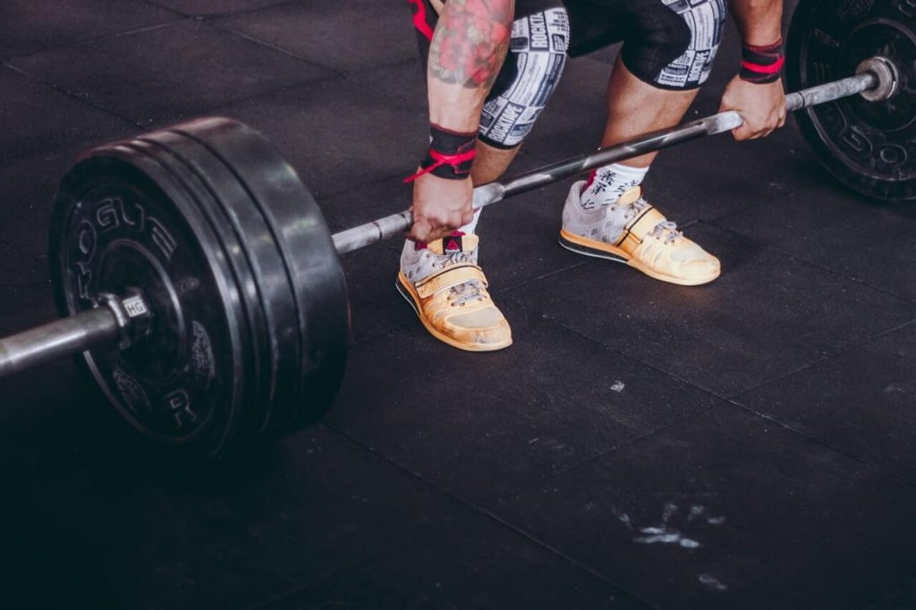 athlete lifting barbell in gym