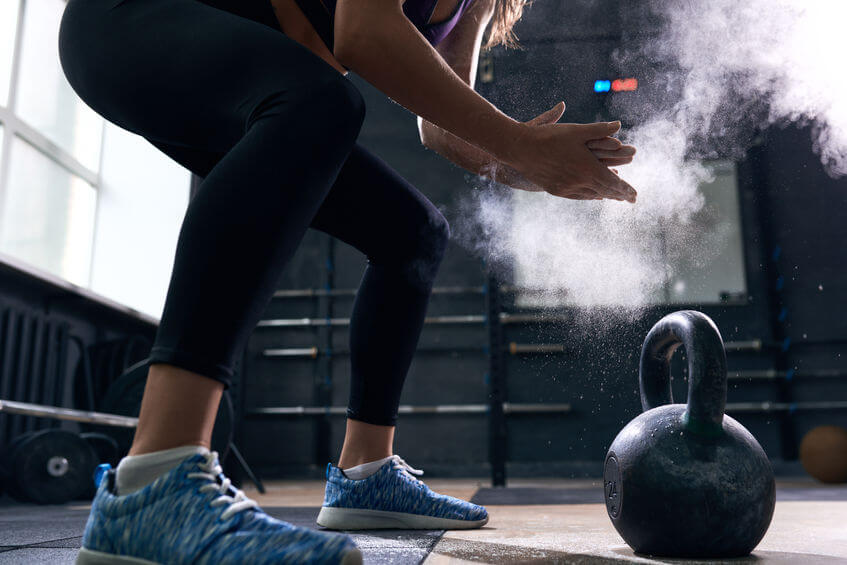woman rubbing hands with gym chalk preparing to lift kettlebells