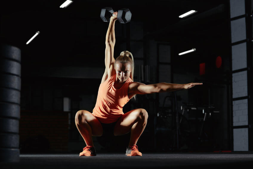 female crossfit athlete exercising with dumbbell