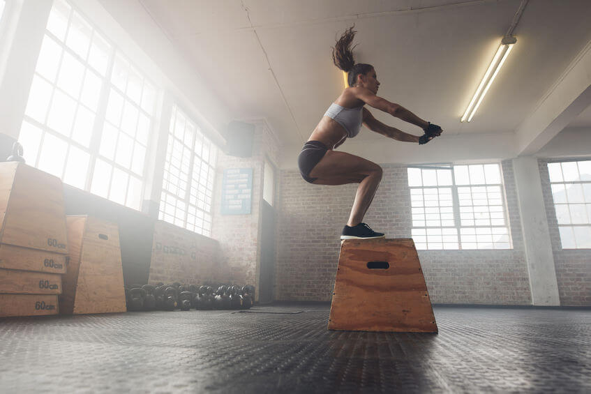 woman doing a box jump exercise at the CrossFit gym