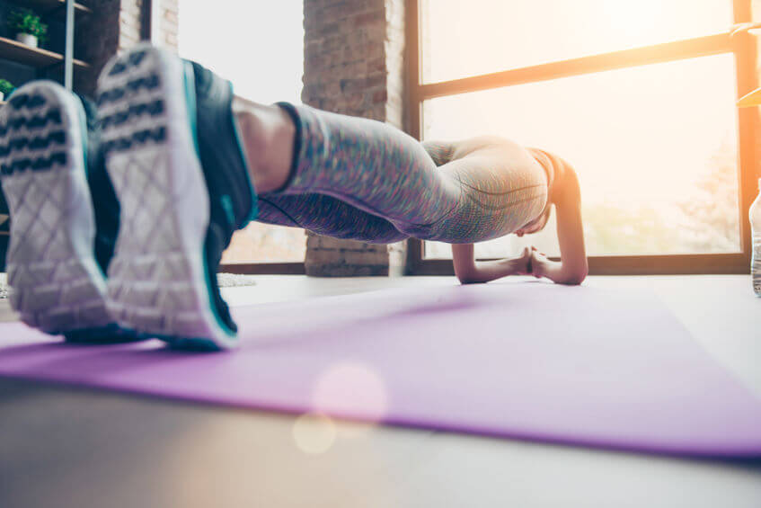 close up photo of womans workout shoes holding plank position