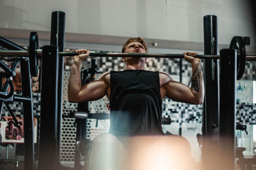man lifting barbell during workout