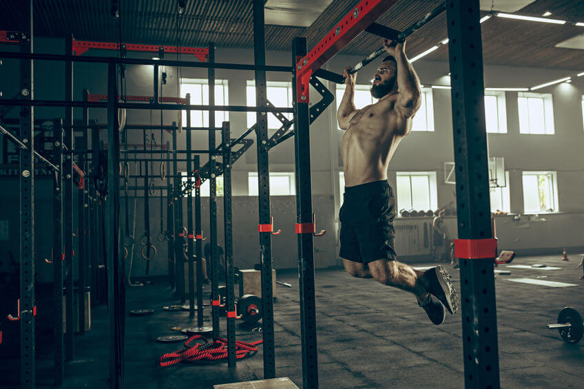 muscular man doing pull ups at CrossFit gym