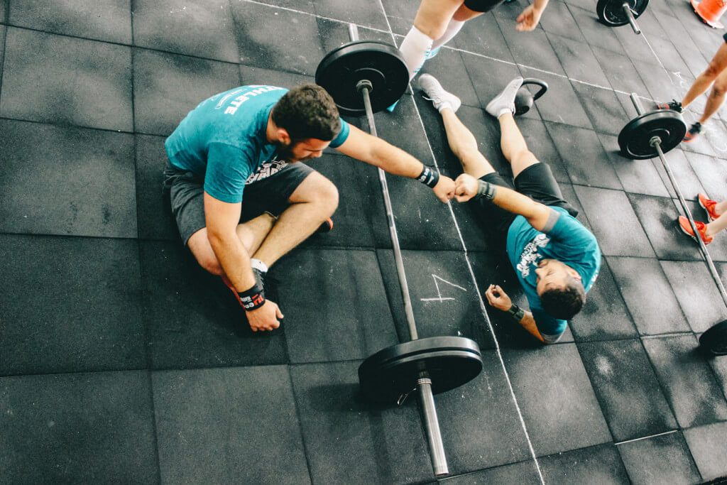 two men in crossfit gym after hard workout