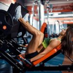 woman doing fitness training on a leg press machine