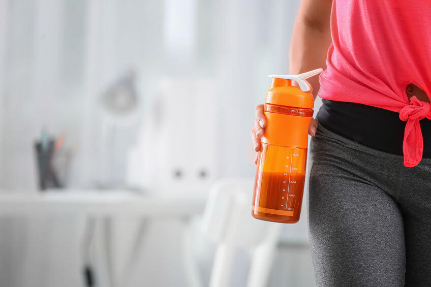 woman holding bottle with supplement workout drink