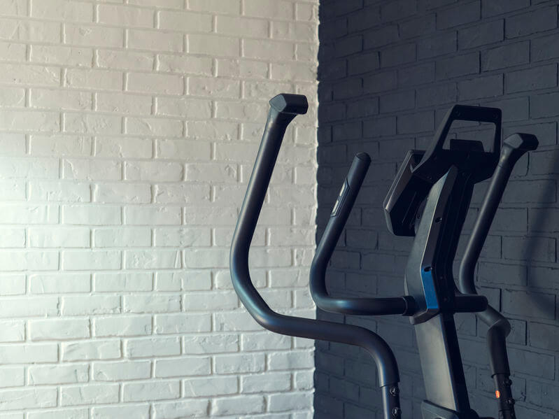 elliptical trainer against a brick wall at home gym