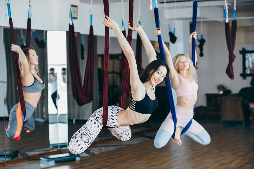 girls do aerial yoga in the gym