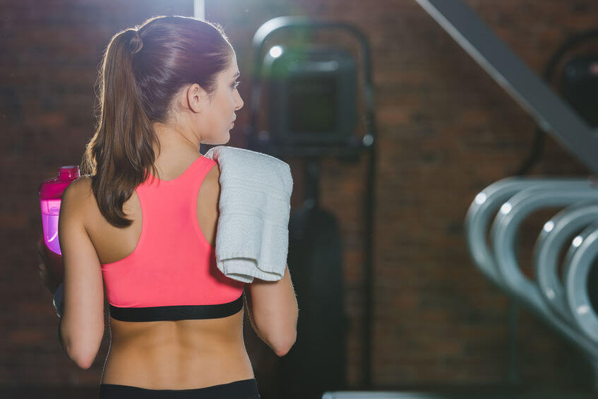 sportswoman holding supplement drink with towel on shoulder at gym