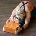 woman doing yoga exercise and using wooden yoga blocks