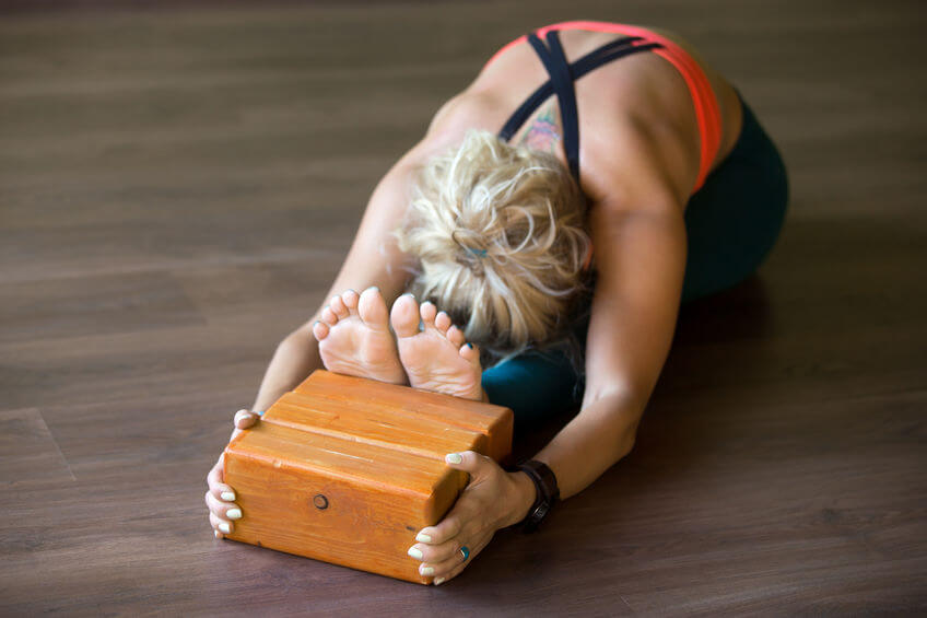 woman doing yoga exercise and using wooden yoga blocks