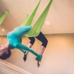 woman performing antigravity yoga with yoga swings