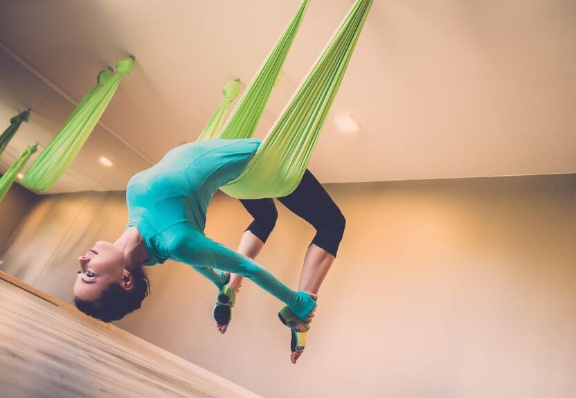 woman performing antigravity yoga with yoga swings