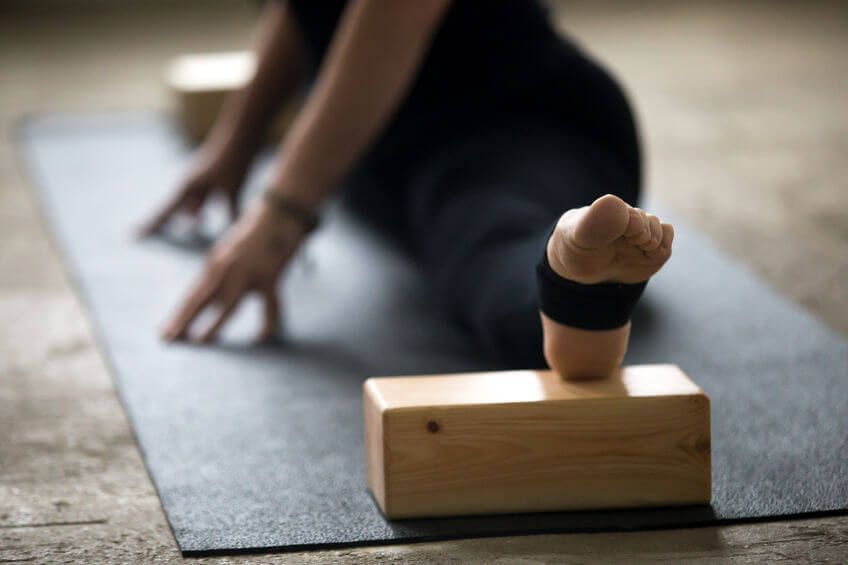 woman practicing yoga pose using blocks for deep stretch