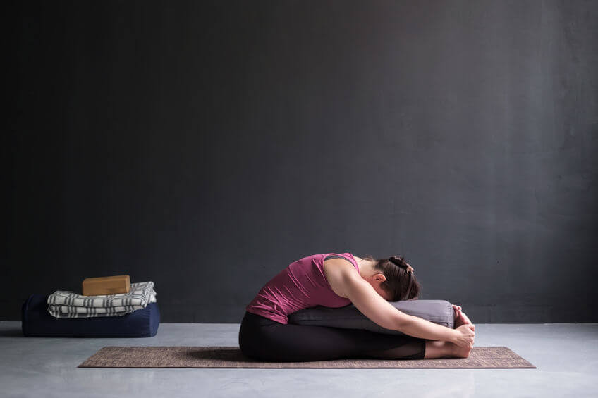 woman practicing yoga with yoga bolster