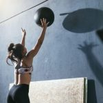 woman training with CrossFit ball at gym