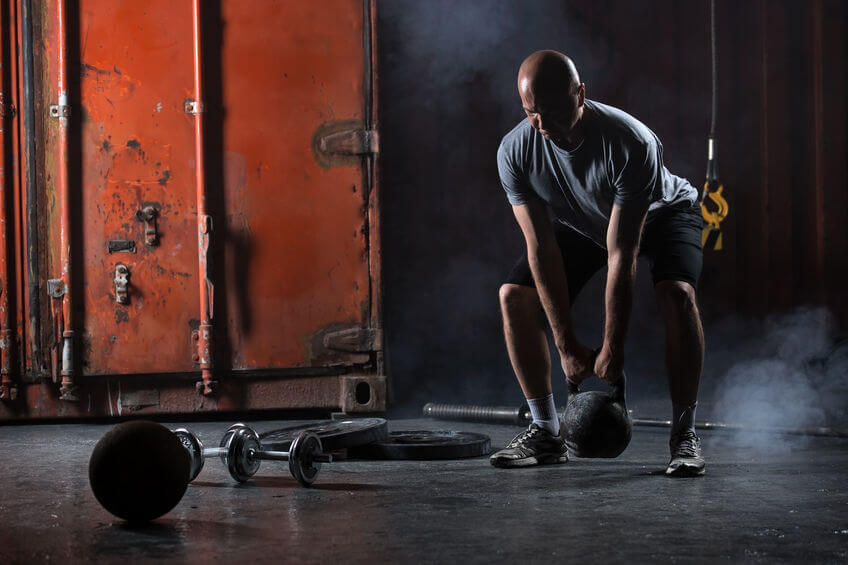 athlete doing squats with kettlebell