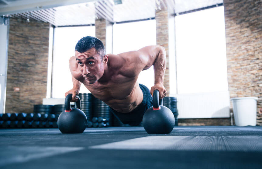 man doing push ups using kettlebells in crossfit gym
