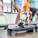senior athletes exercising on step platforms at gym