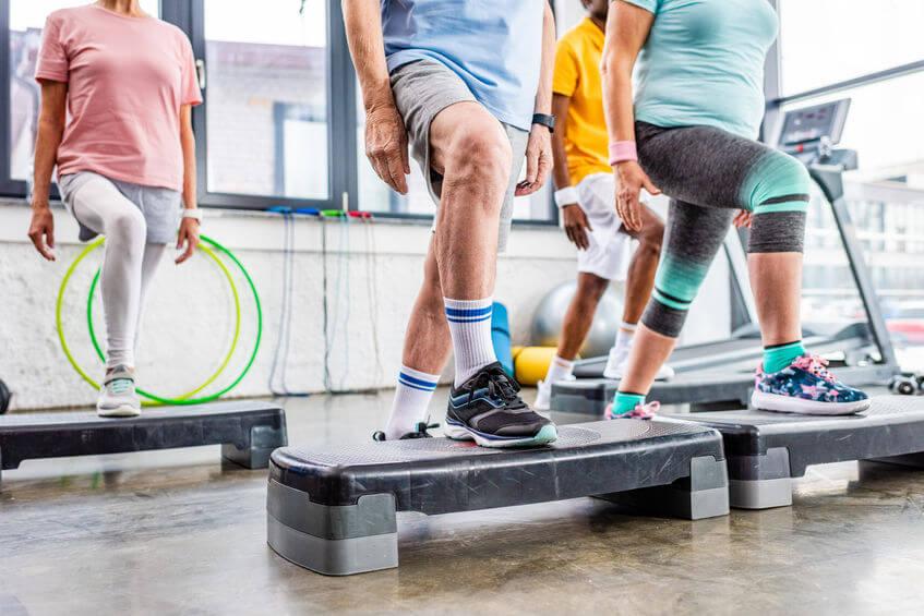 senior athletes exercising on step platforms at gym