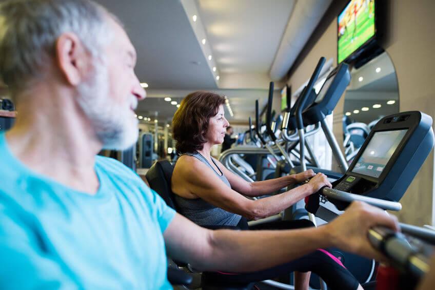 senior couple in gym doing cardio work out on recumbent bikes