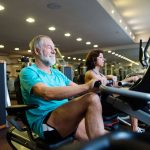 senior couple in gym doing cardio work out recumbent bikes