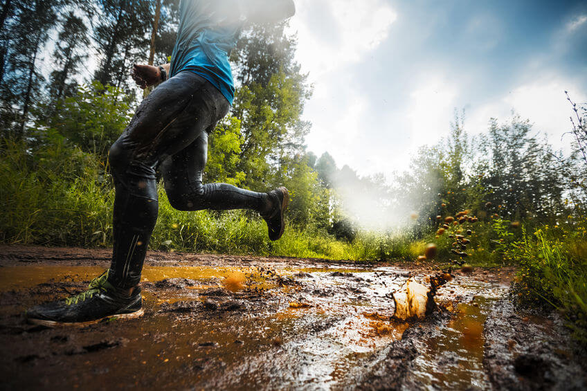 trail runner moving through the dirty puddle