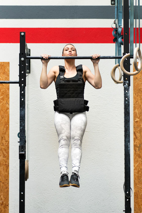 woman doing pull-ups on a bar wearing weighted vest