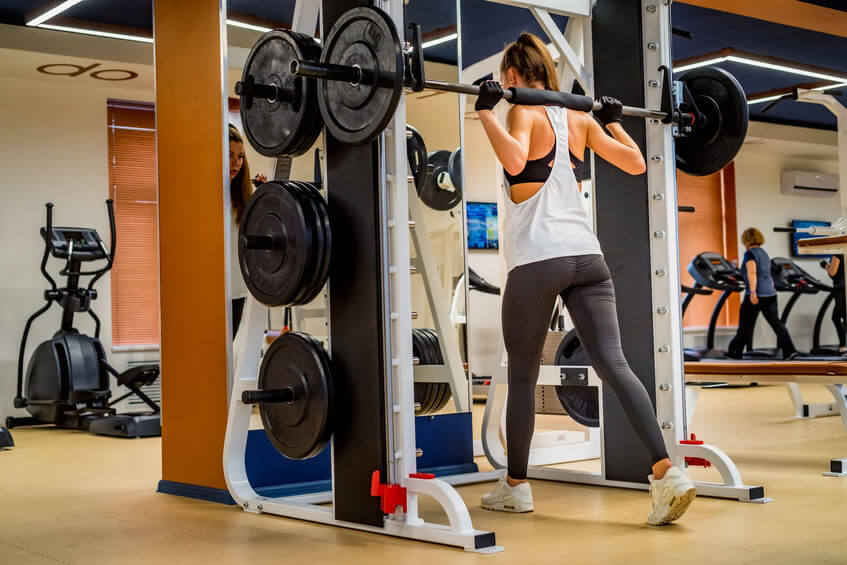 woman doing squats on smith machine in gym