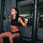 woman doing squats with a barbell in smith machine