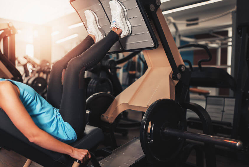 woman exercise on leg press at the gym