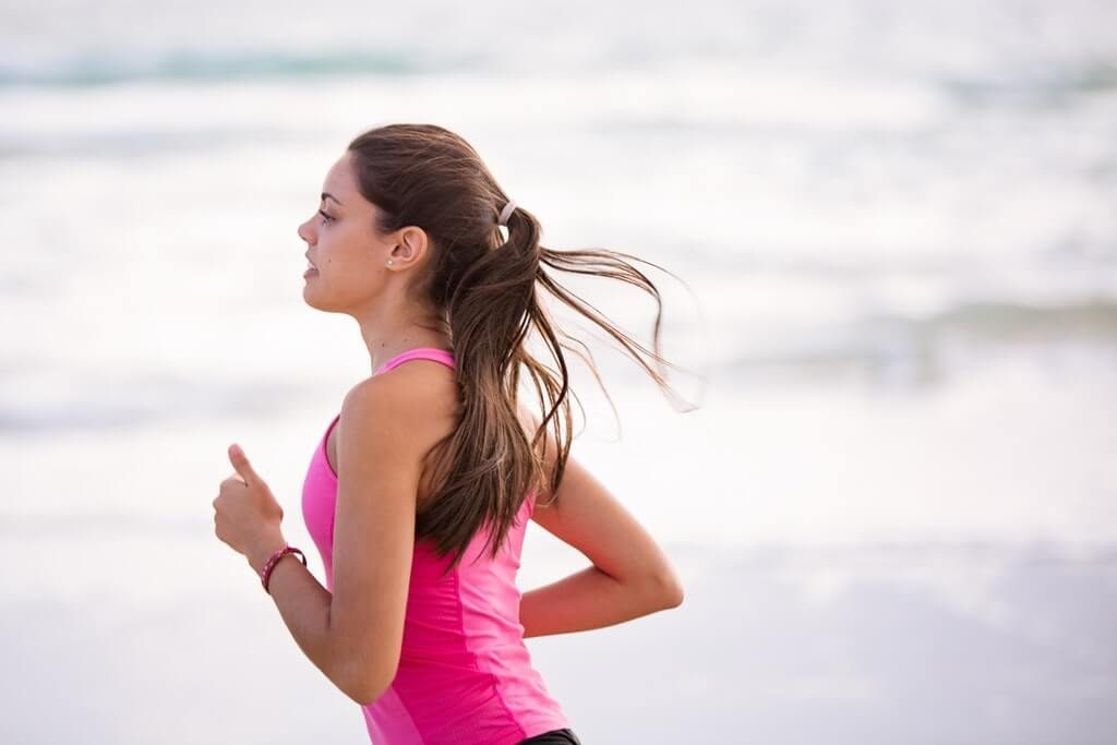 woman slowly jogging on the beach