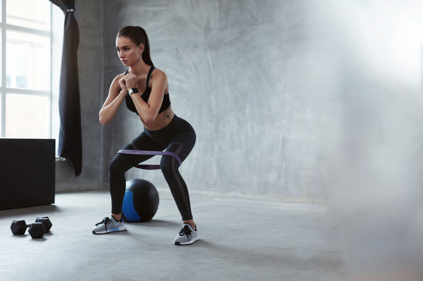woman squatting with resistance band