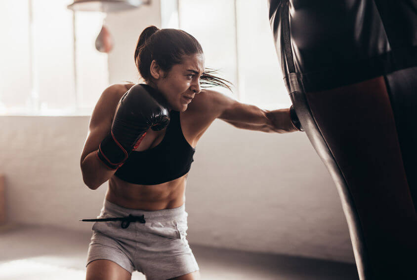 female boxer hitting punching bag