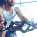 man cycling at gym using exercise bike