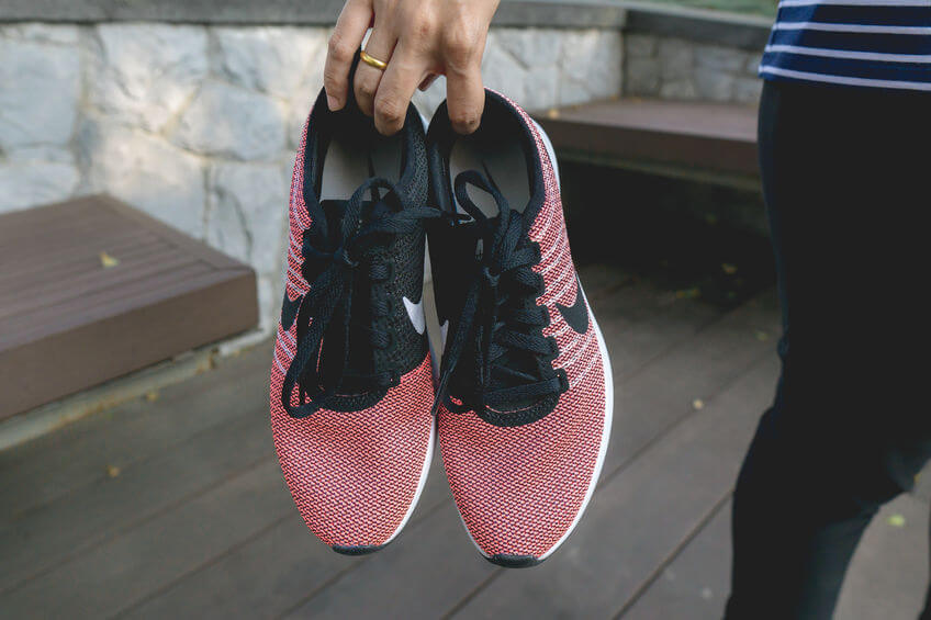 woman holding pair of pink nike running shoes