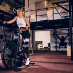 woman training on the air resistance exercise bike in the gym.